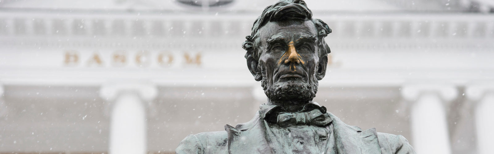A light snow falls on the Abraham Lincoln statue in front of Bascom Hall